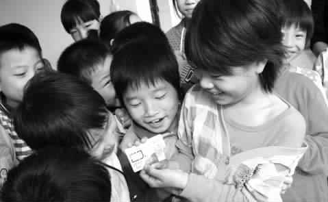 """图一:""""八一""""希望小学留守儿童喜领""""爱心电话卡 ..."""